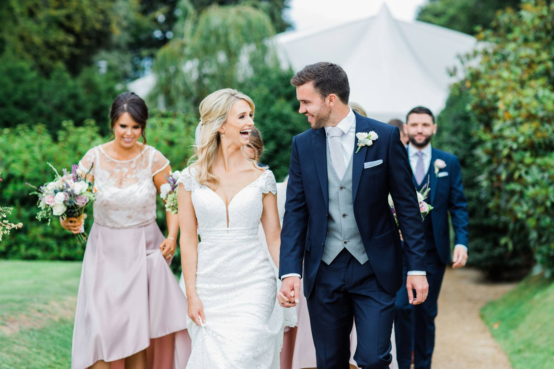 Bride and groom holding hands and walking and laughing together in Tinakilly House