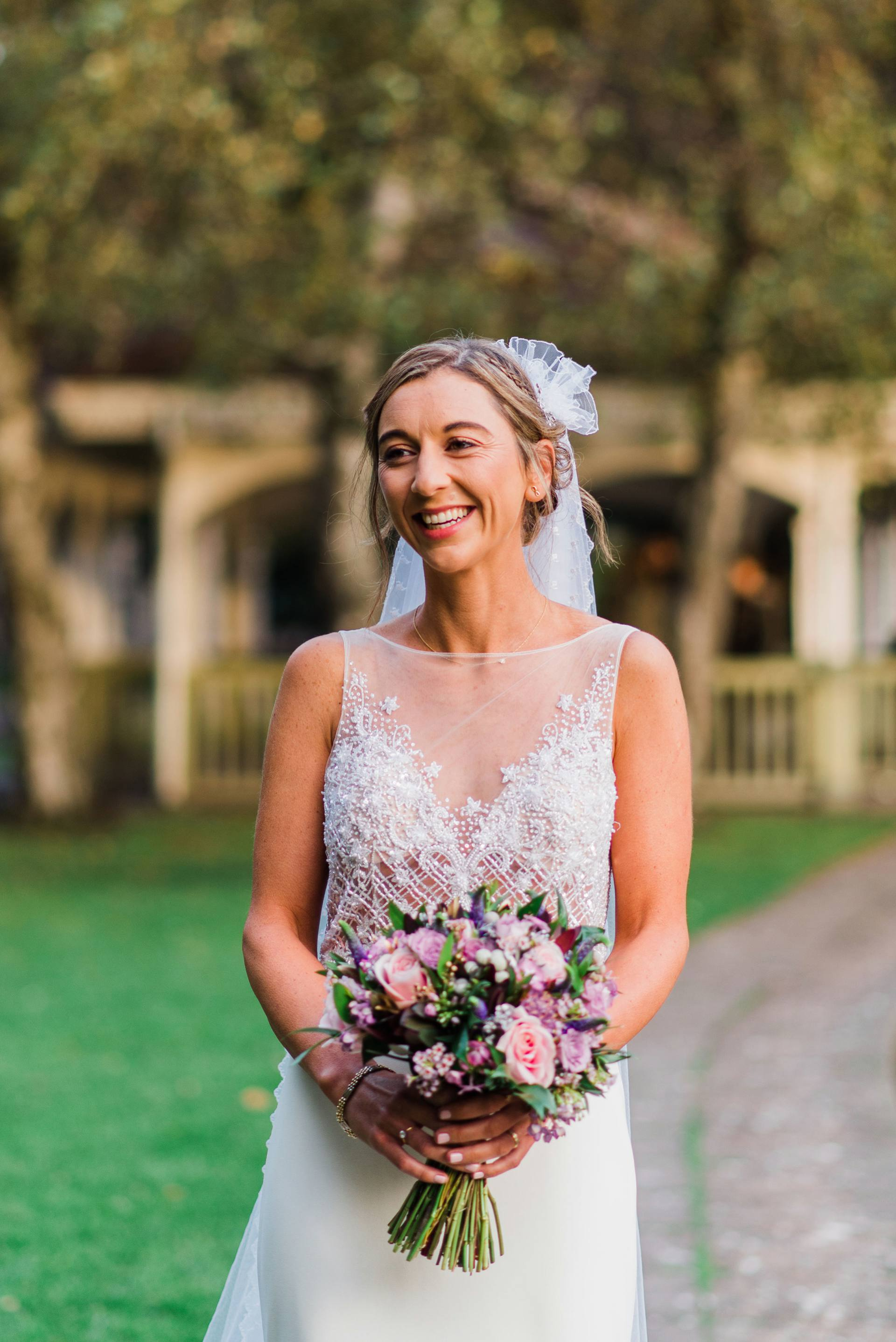 Smiling Bride holding purple flowers