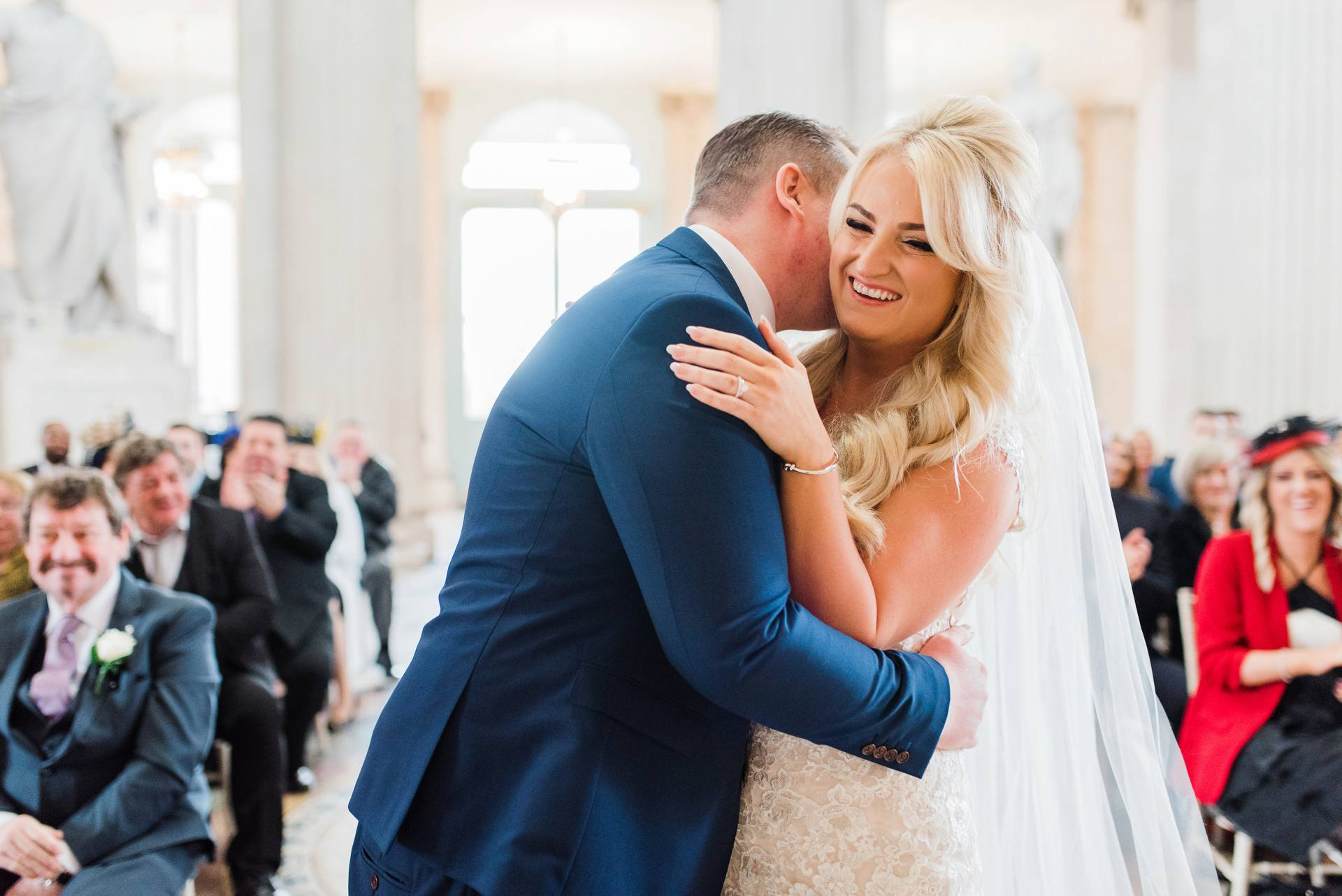 Groom hugging blonde bride in City Hall Dublin