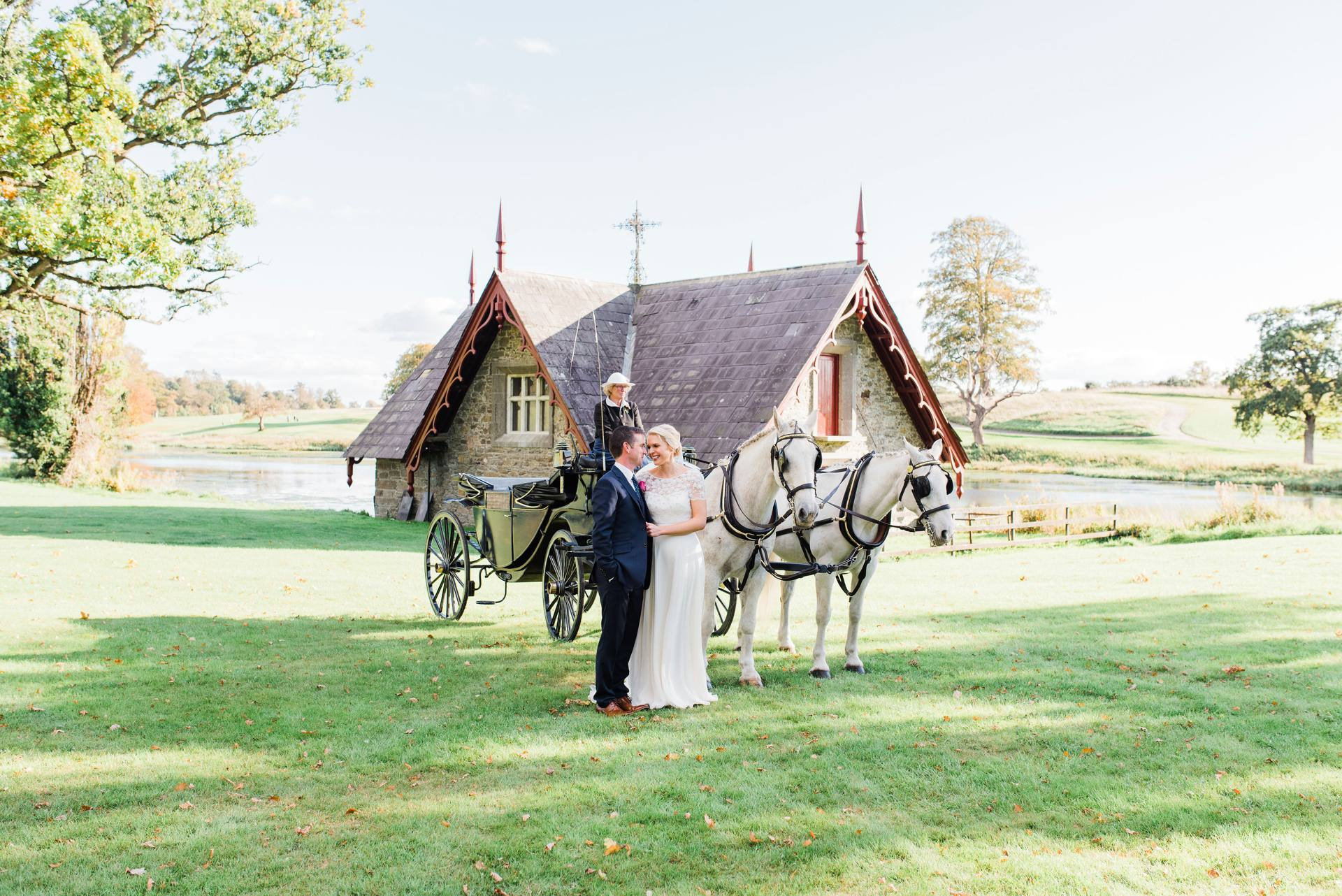 Bride and groom with horse drawn carriage beside the boat house at Carton House
