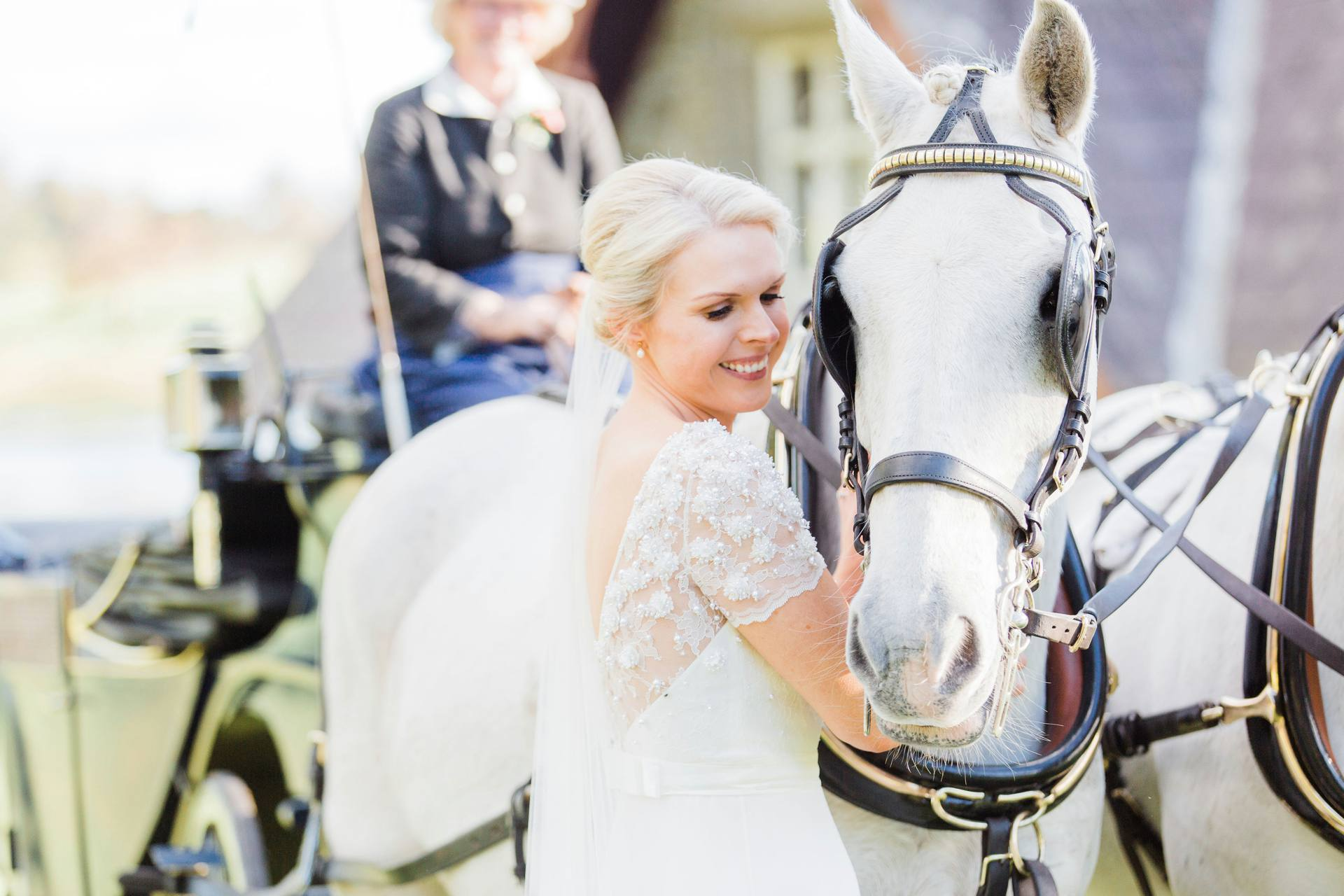 Bride smiling beside white horse