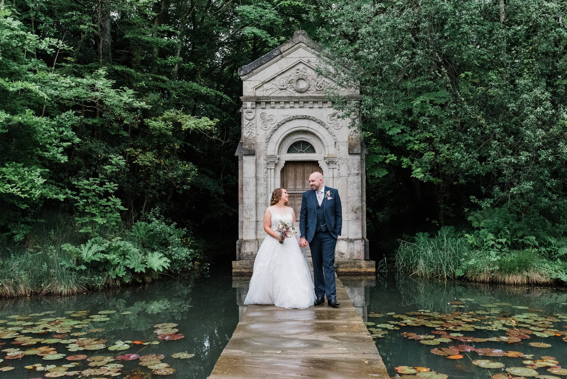 Bride and groom walking hand in hand beside a lily pond at Cliff at Lyons
