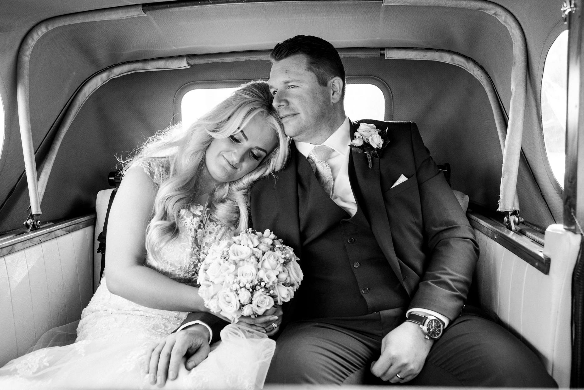 Bride and groom sitting together in the back of a car
