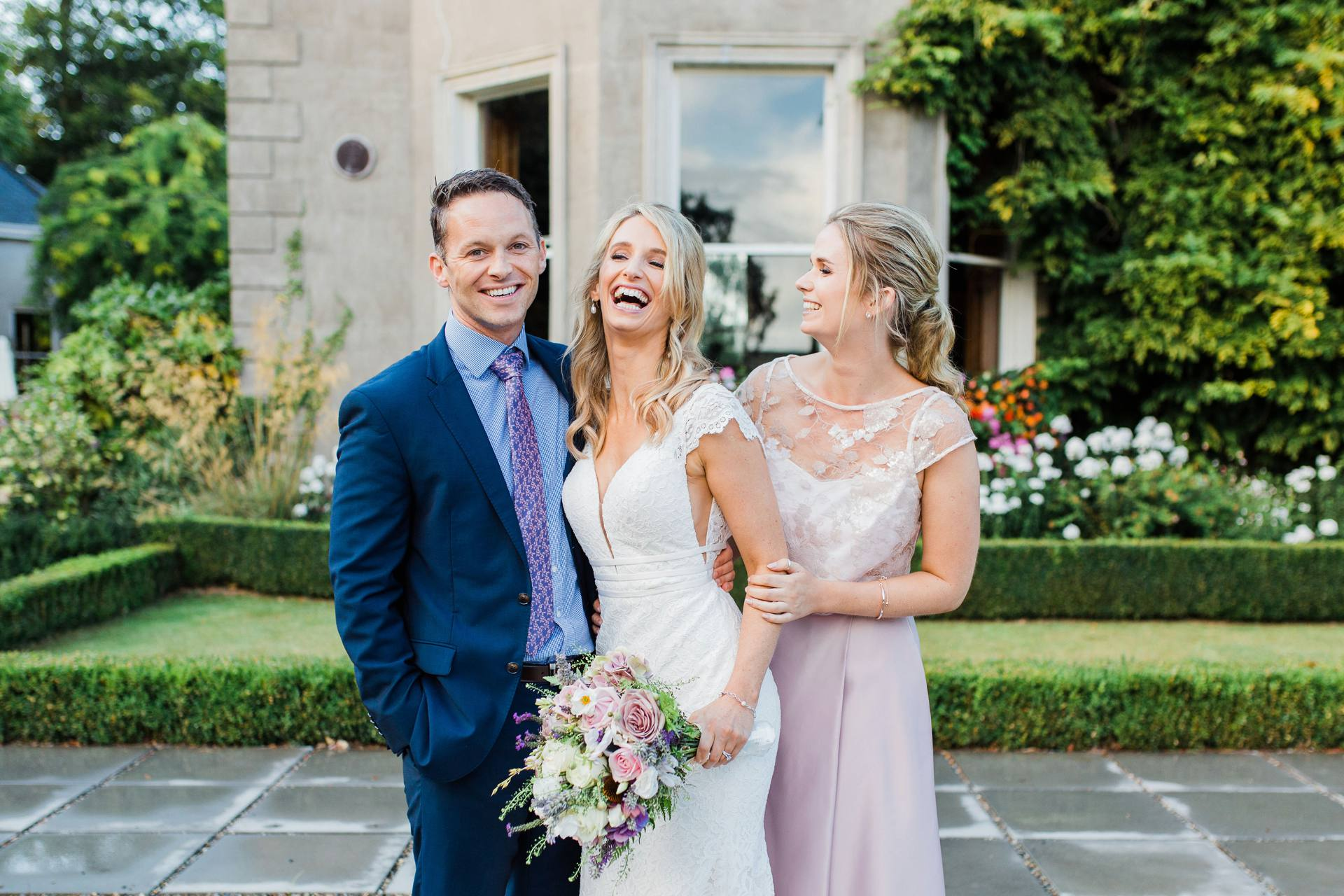 Bride laughing with brother and sister