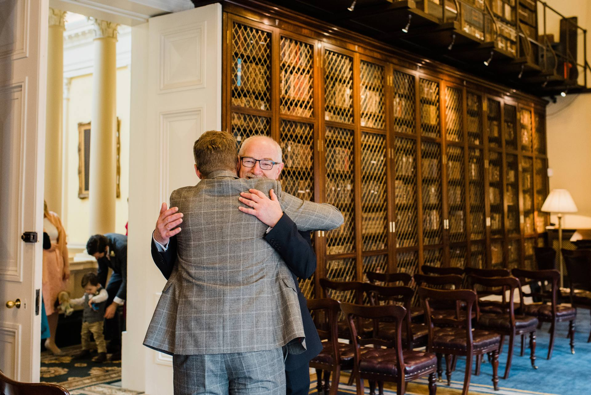 Groom hugging father in a library