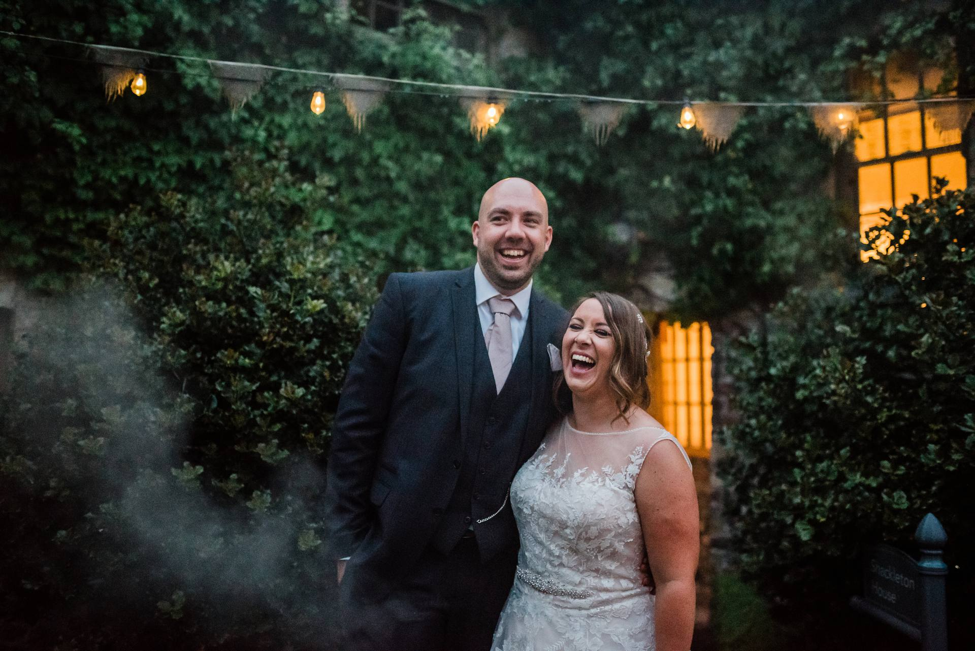 Bride and groom laughing together at night surrounded by smoke