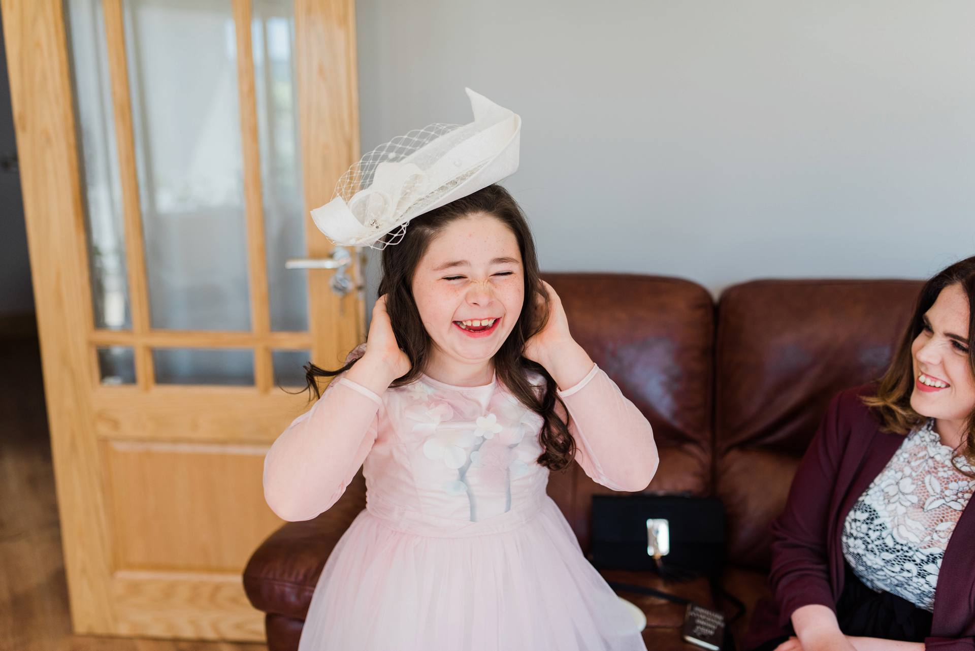 Flower girl trying on a hat and laughing