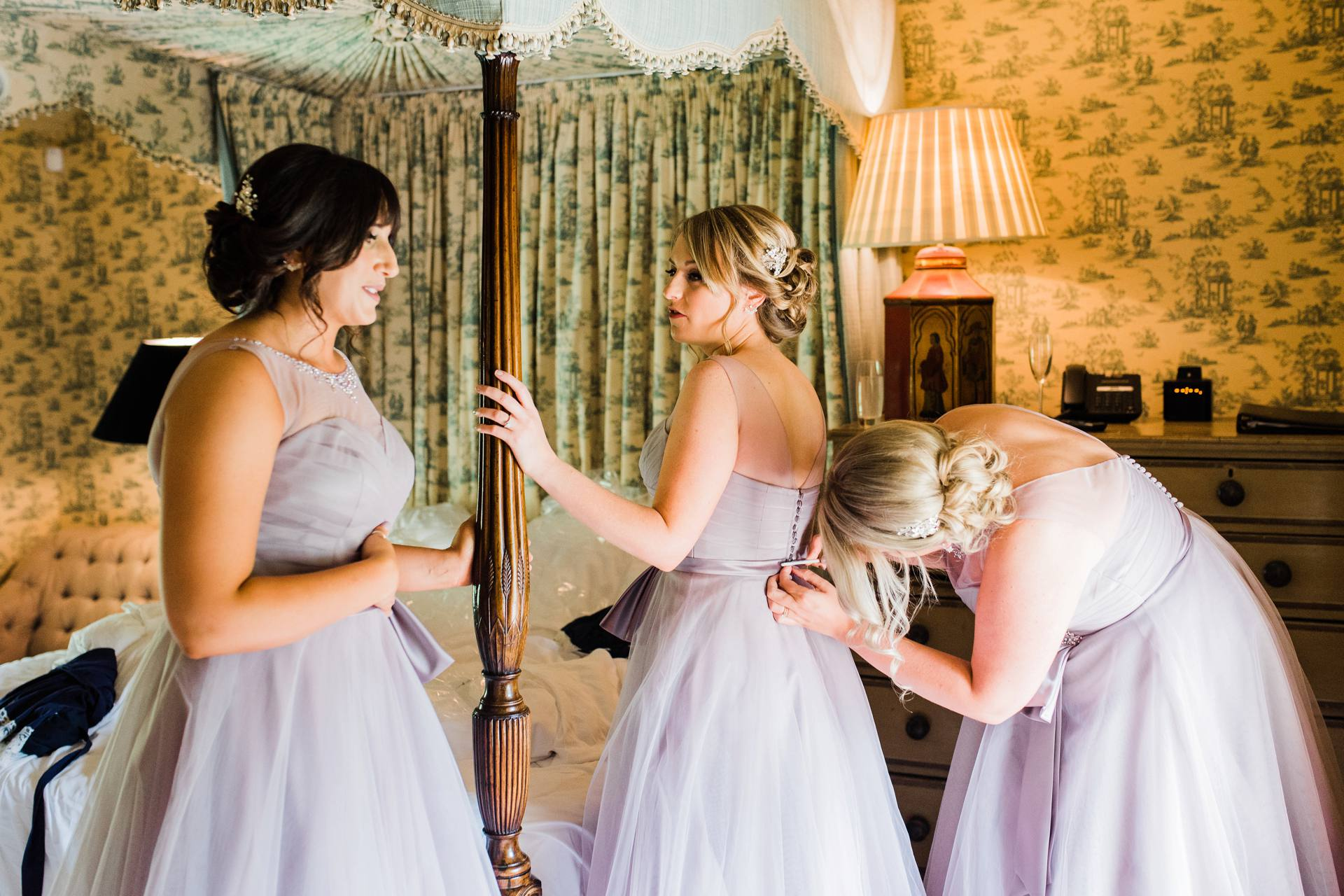 Bridesmaids putting on lavender dresses together