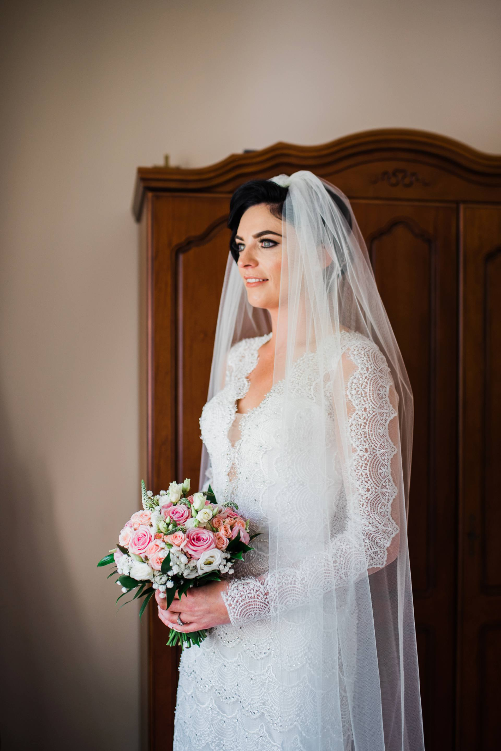 Bridal portrait with bride holding pink flowers