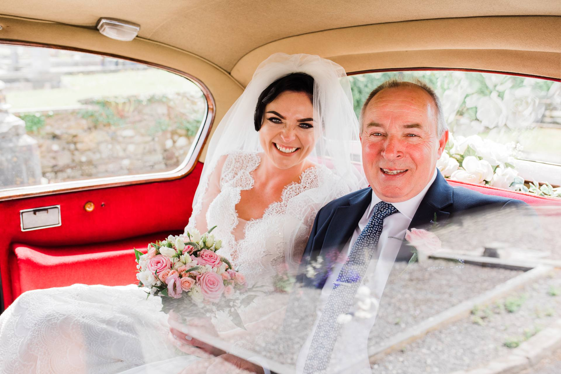 Bride with father in a car