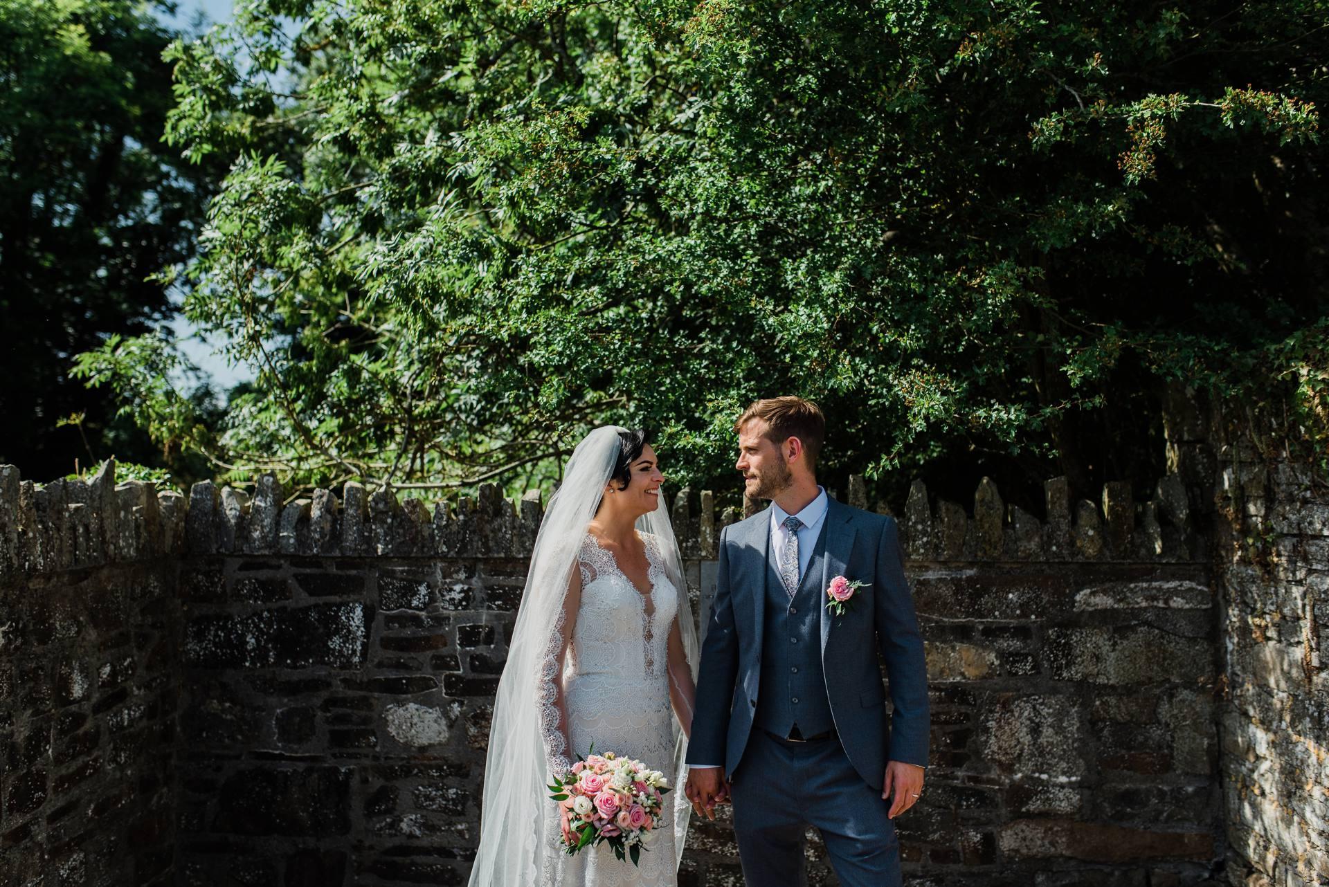Bride and groom beside trees