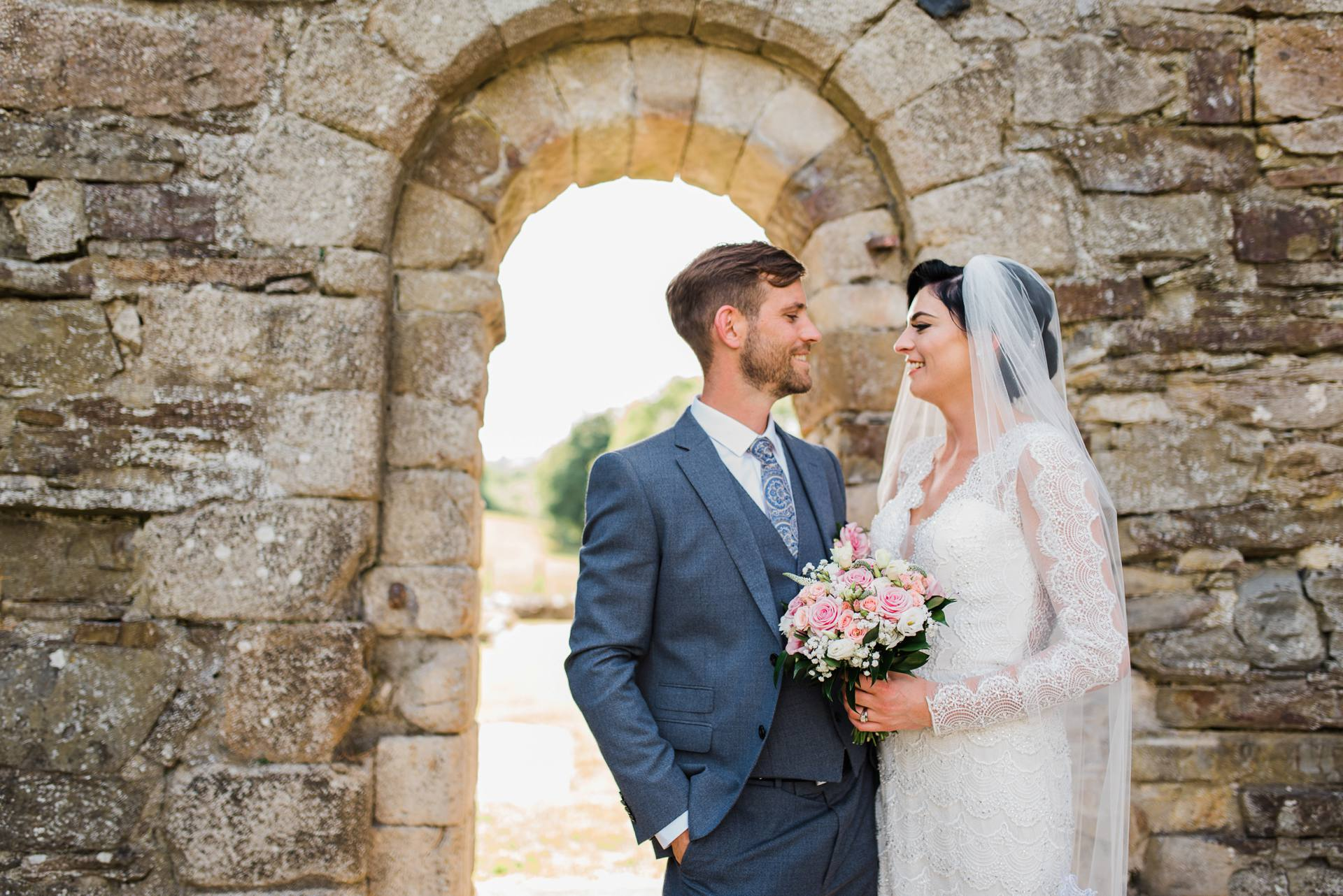 Bride and groom standing in stone archway