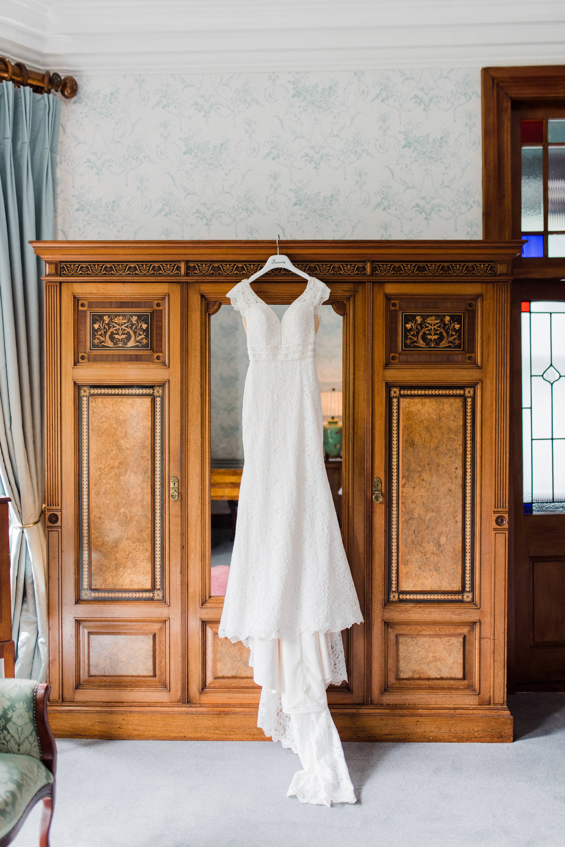 Lace wedding dress hanging on wardrobe