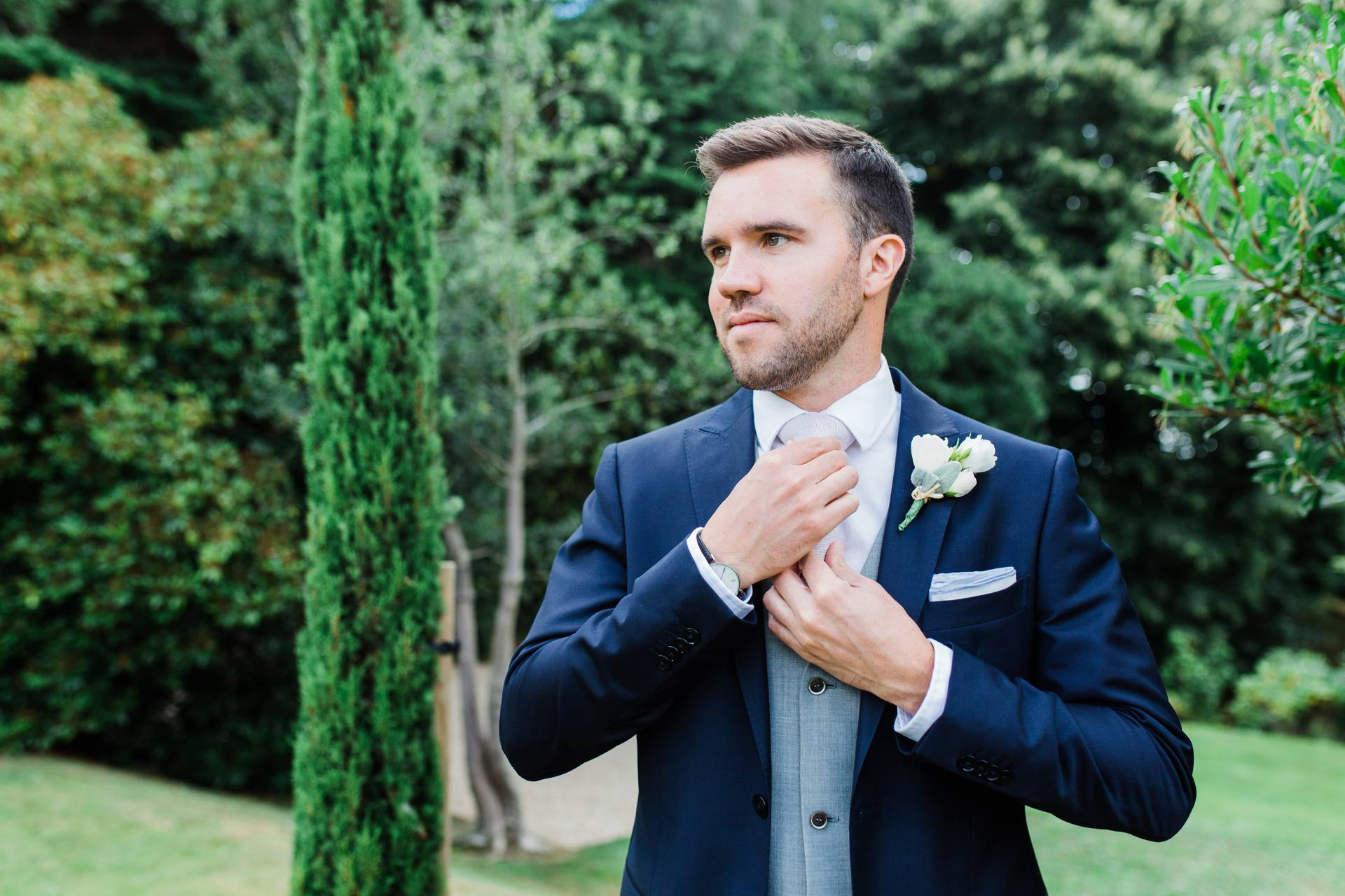 Groom straightening his tie