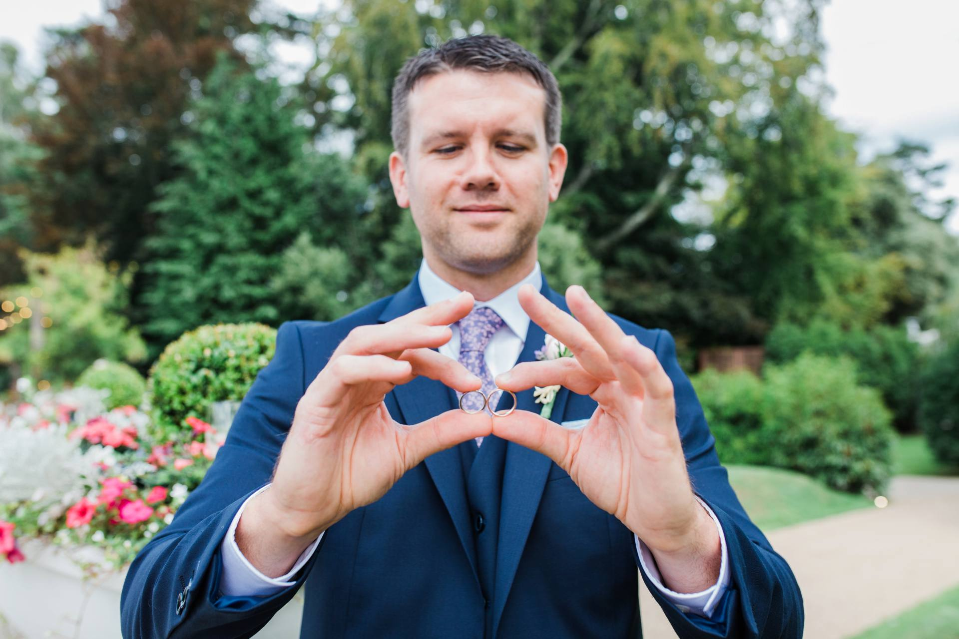 Groomsman holding up wedding rings