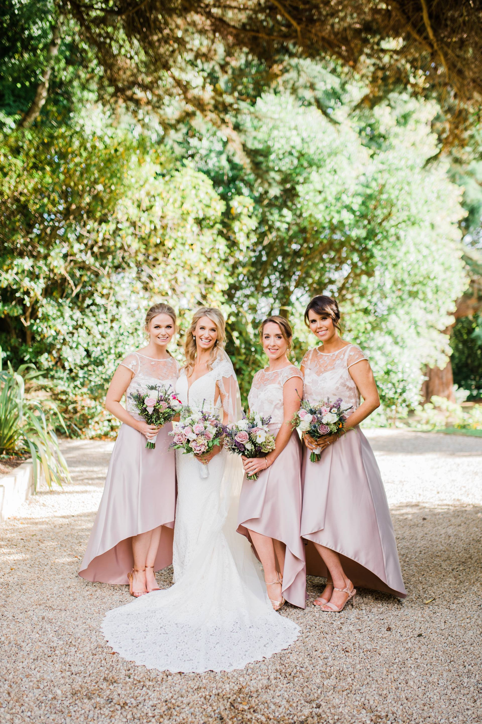 Bride with bridesmaids standing under a tree