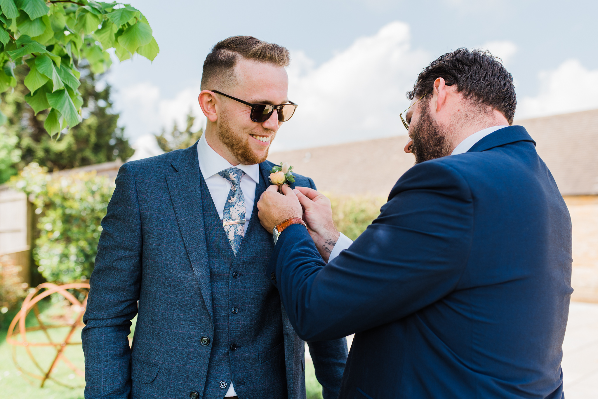 Groom and Best man putting on boutonniere