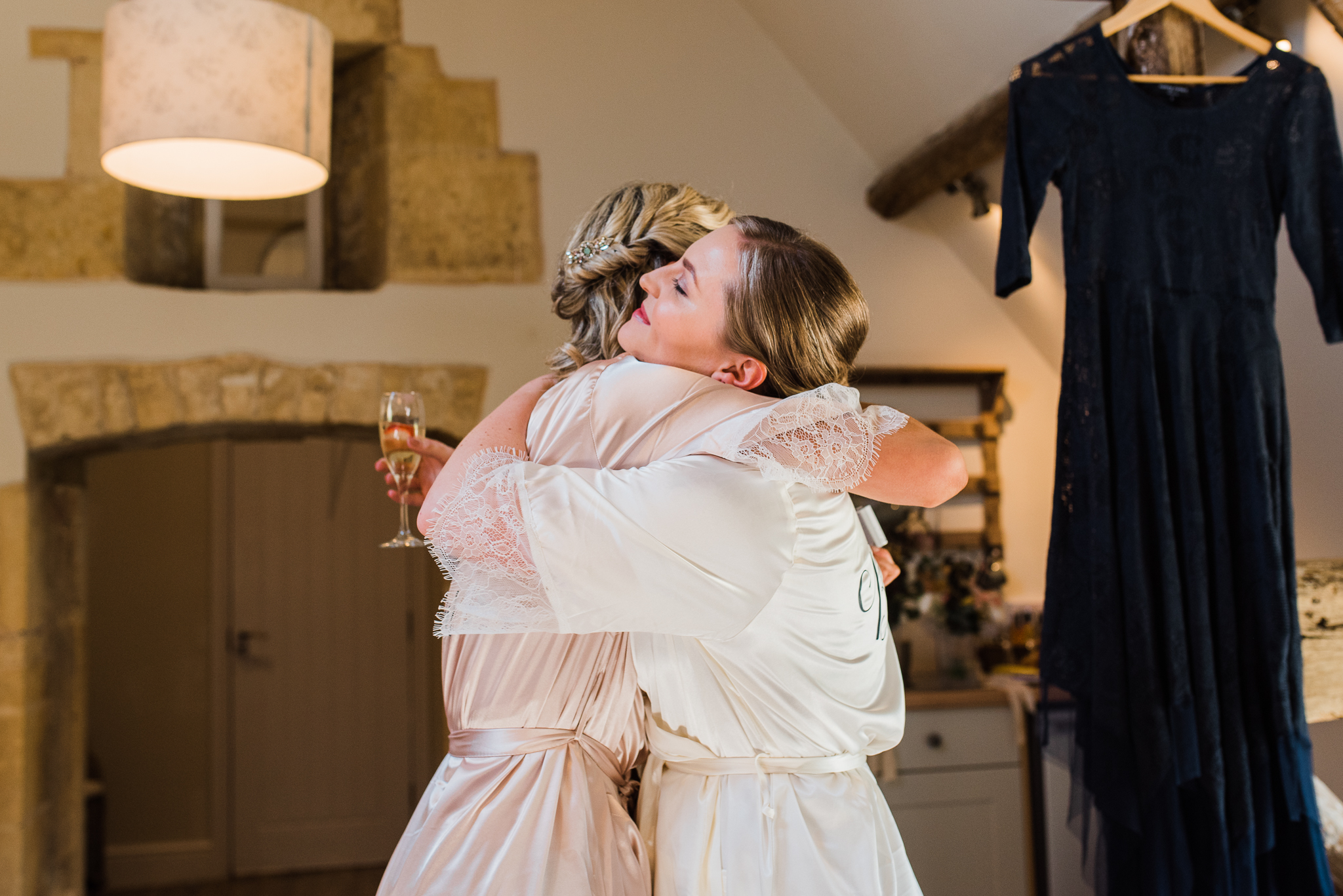 Bride hugging bridesmaid in Lapstone Barn