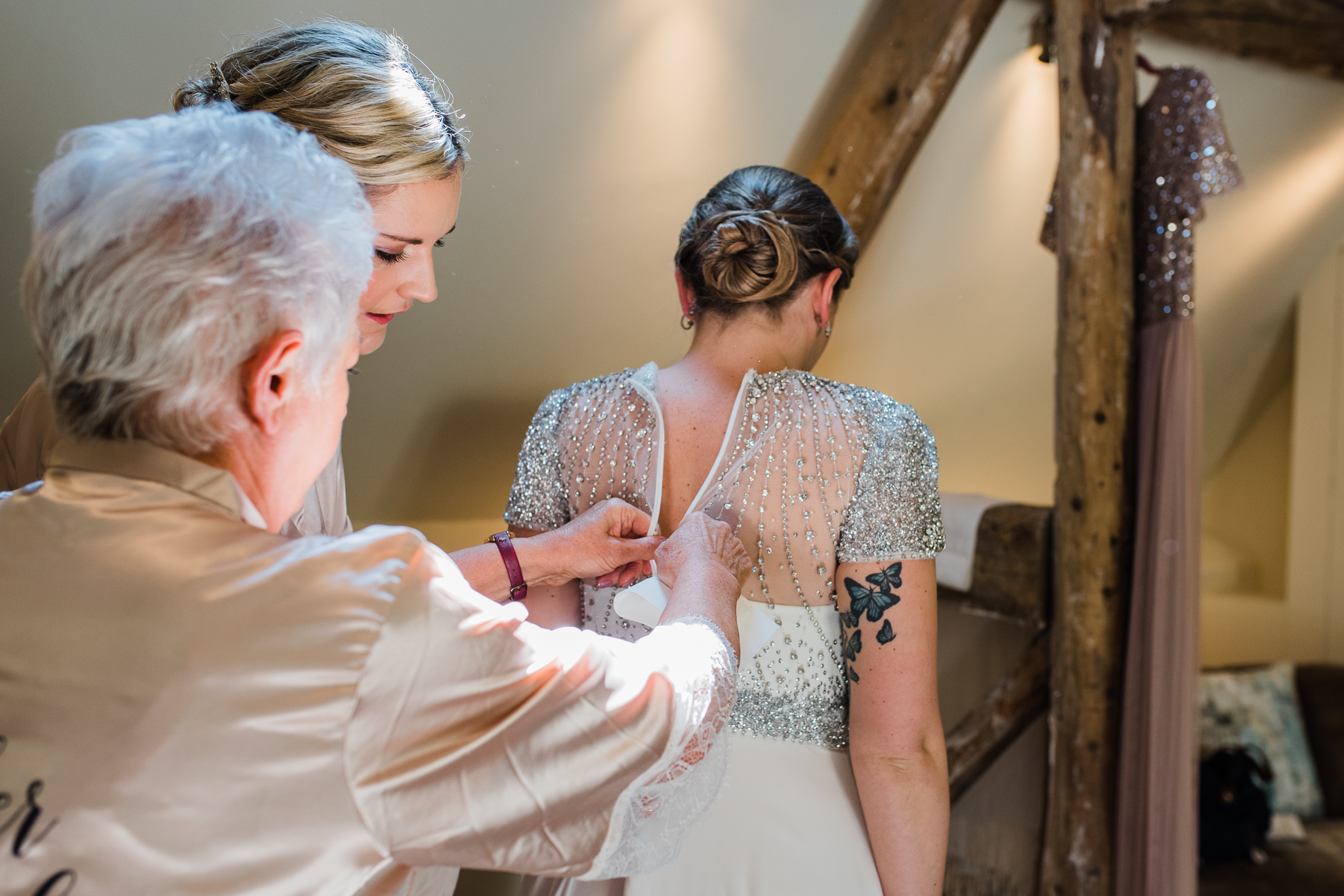 Zipping up brides dress in Lapstone Barn