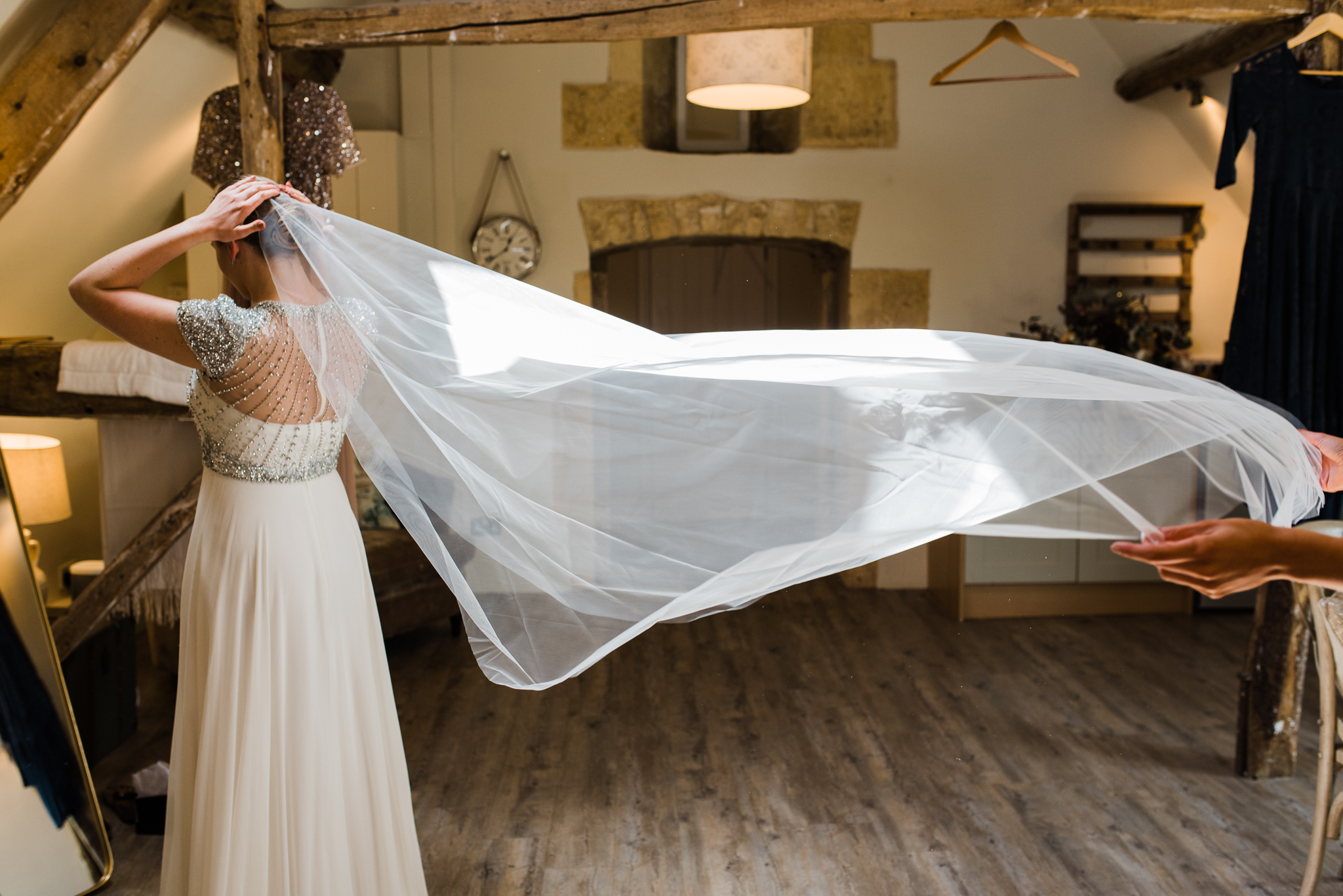 Bride putting on her veil in Lapstone Barn