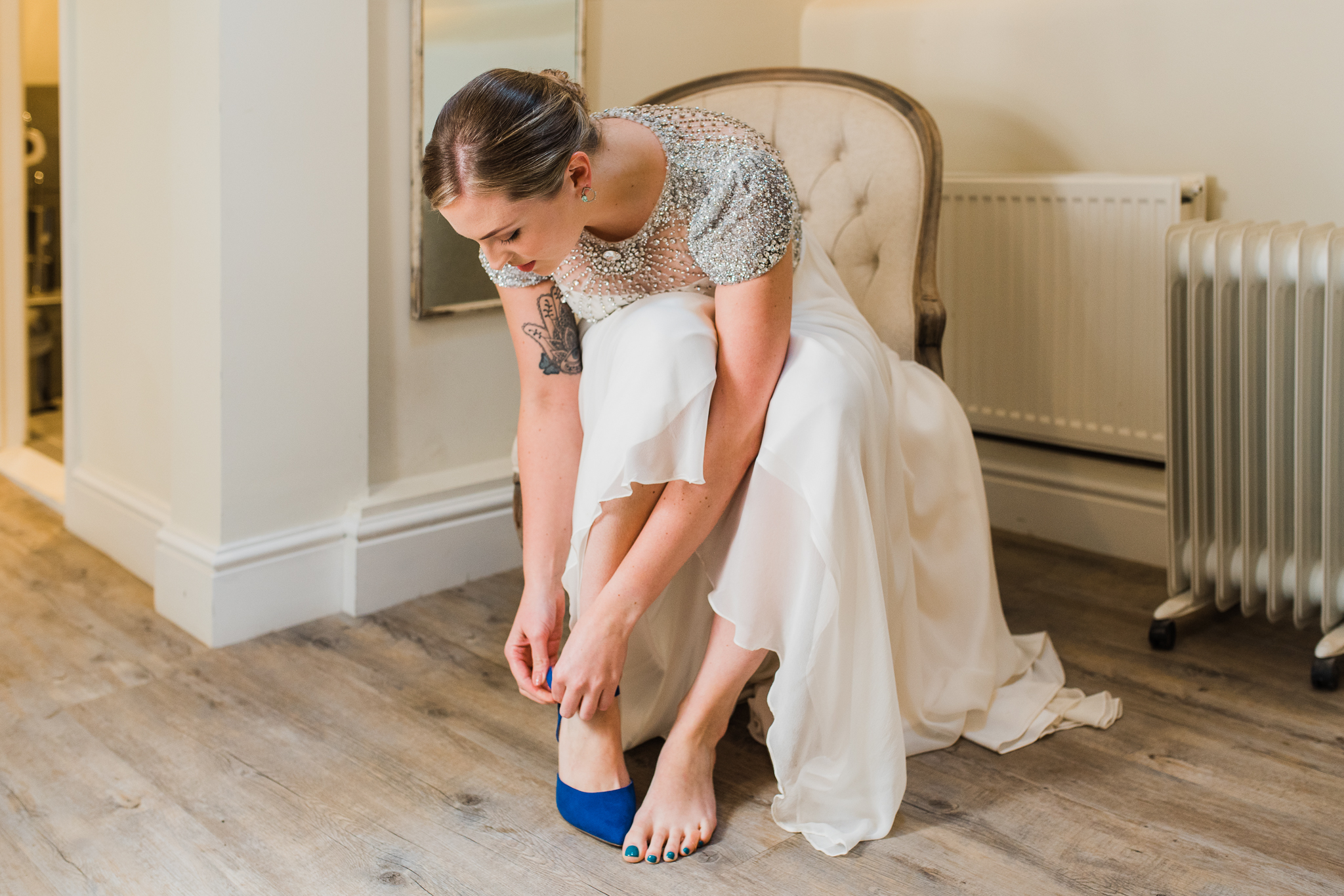 Bride putting blue shoes on in Lapstone Barn wedding