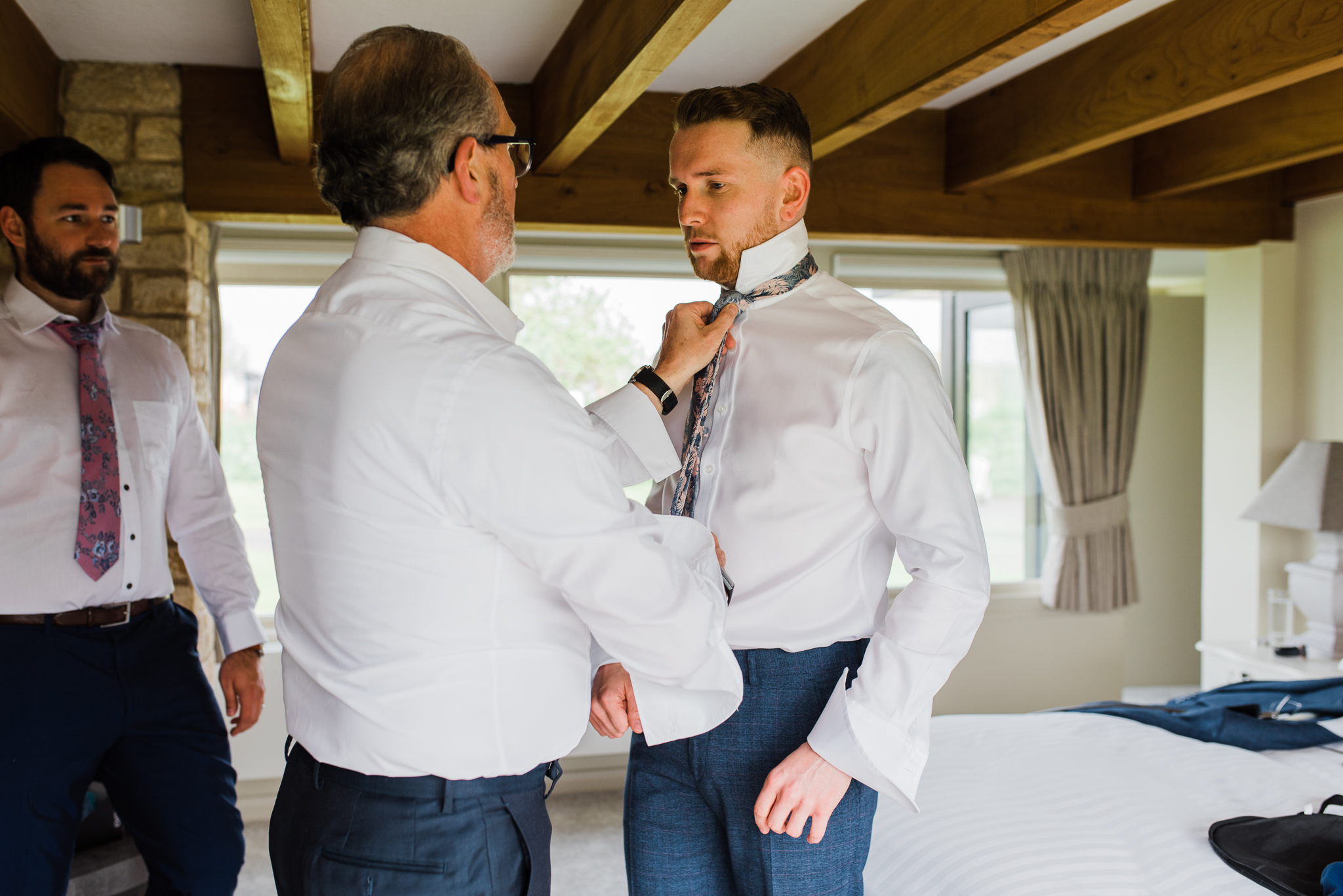 Groom putting tie on