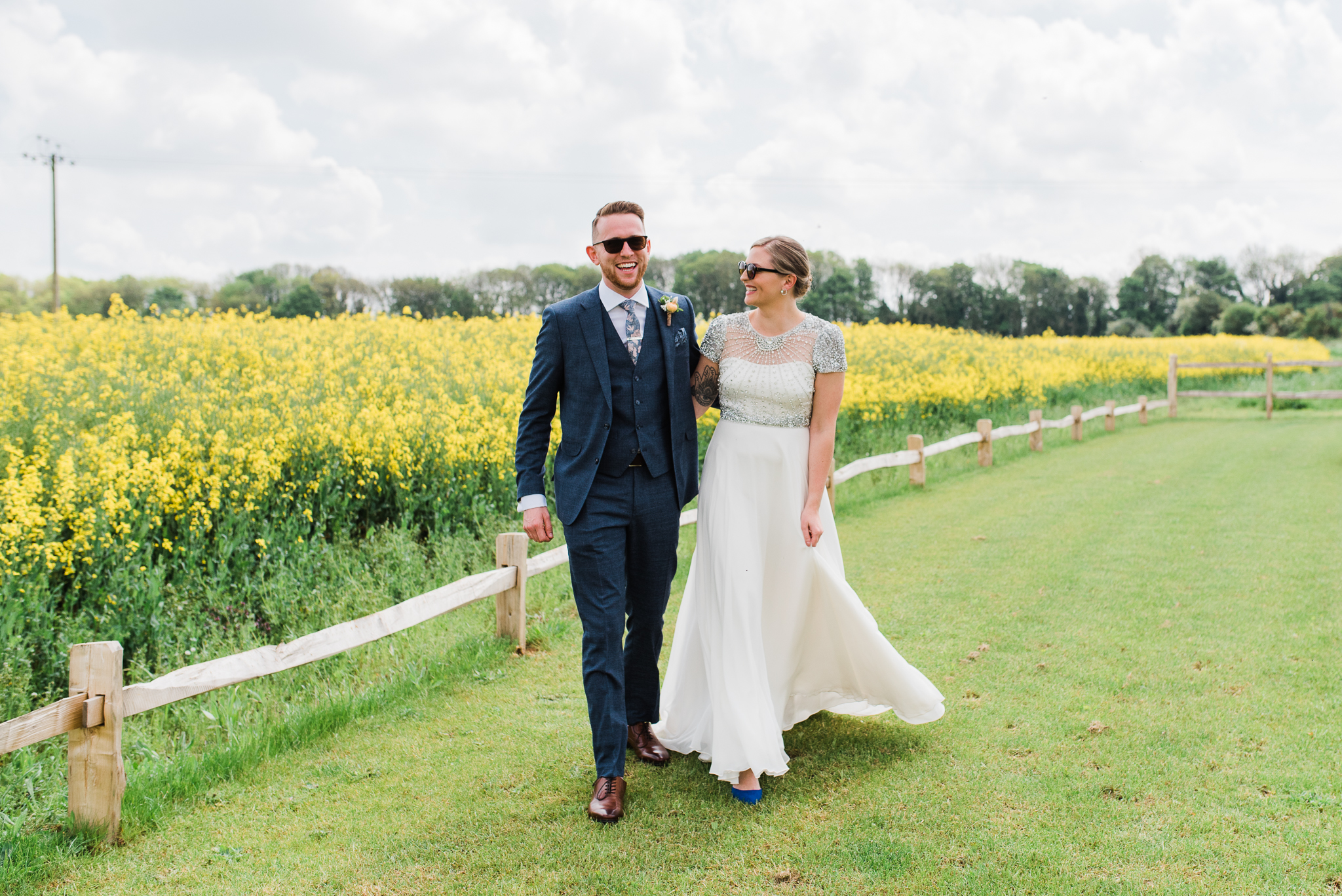 Bride and groom walking beside rapeseed field