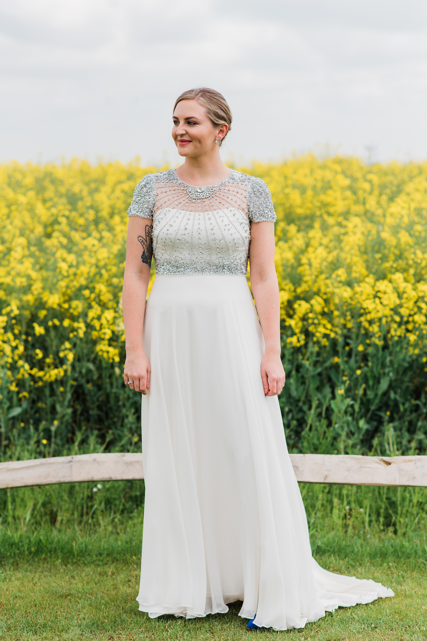 Bride standing beside rapeseed field in Jenny Packham dress