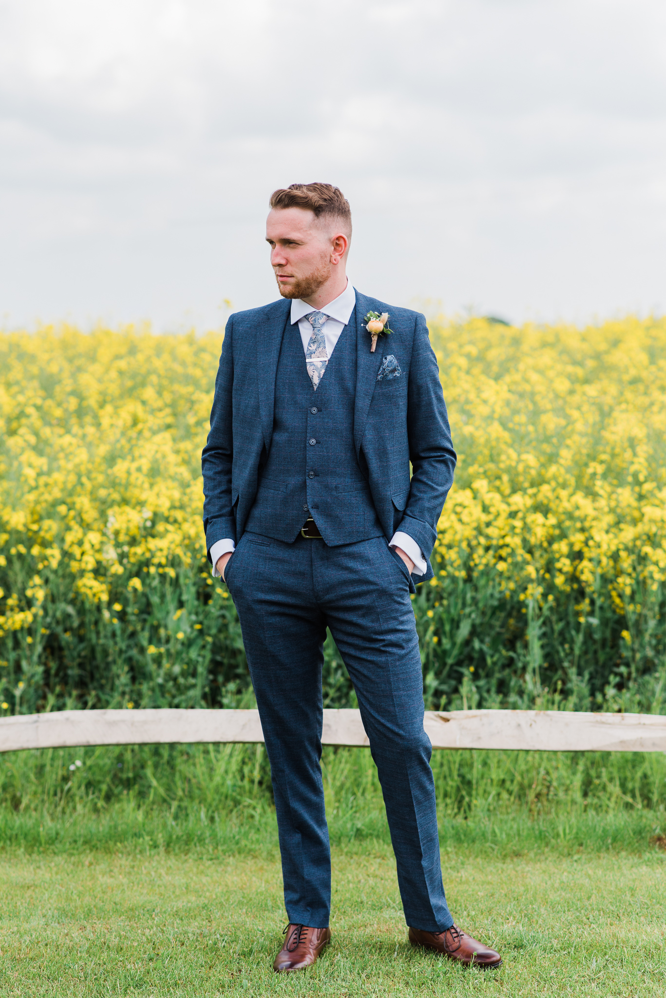 Groom standing beside rapeseed field