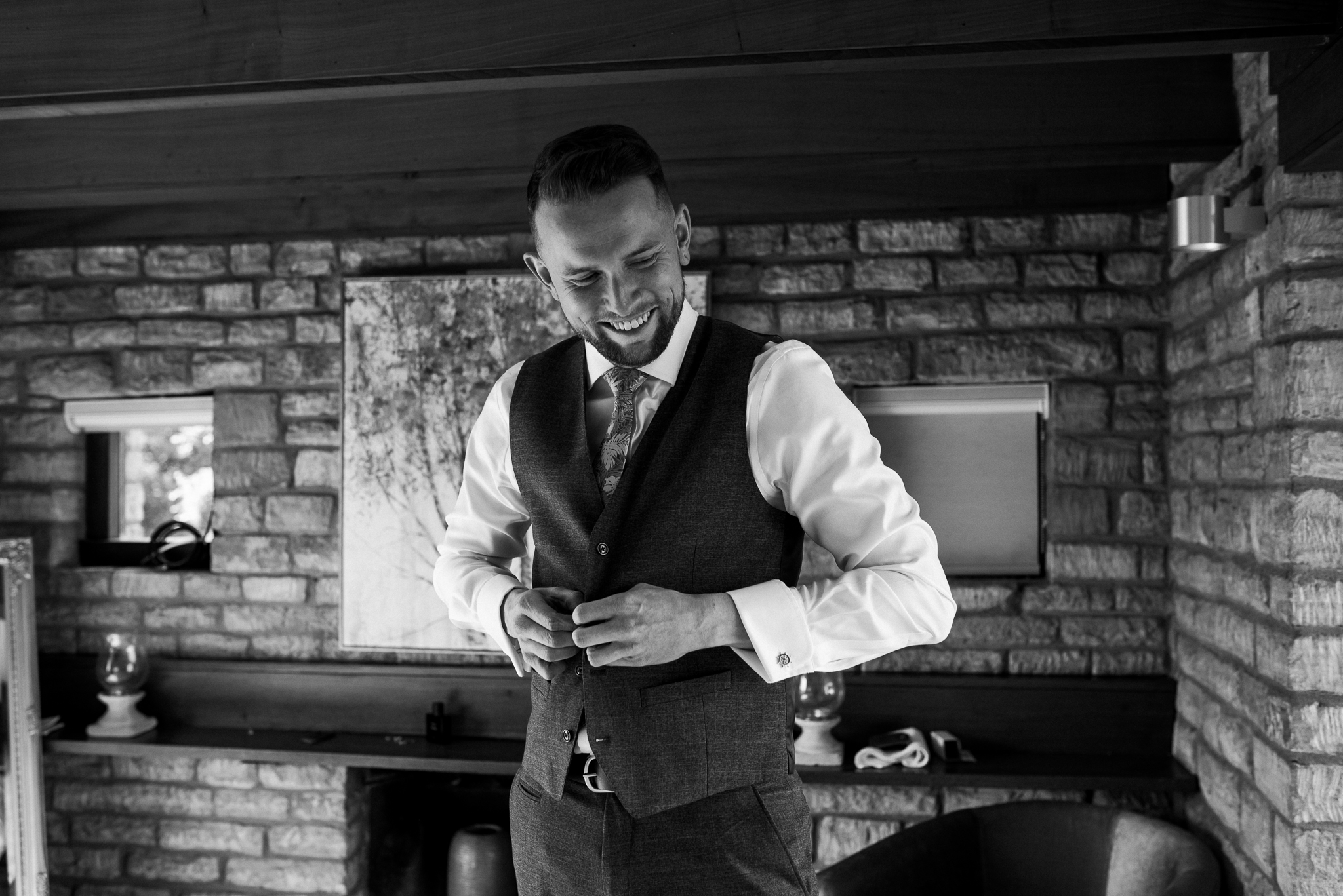 Groom laughing and buttoning waistcoat