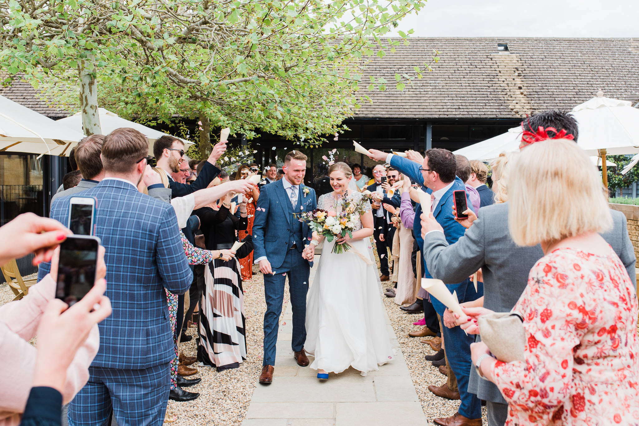 Guest throwing confetti at bride and groom in Lapstone Barn