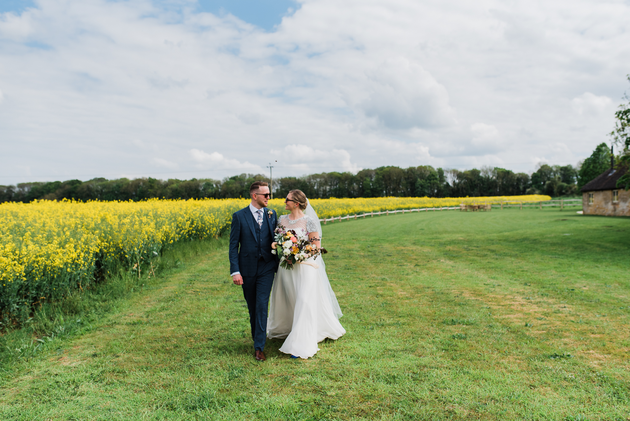 Bride and groom walking at lapstone barn beside rapeseed field