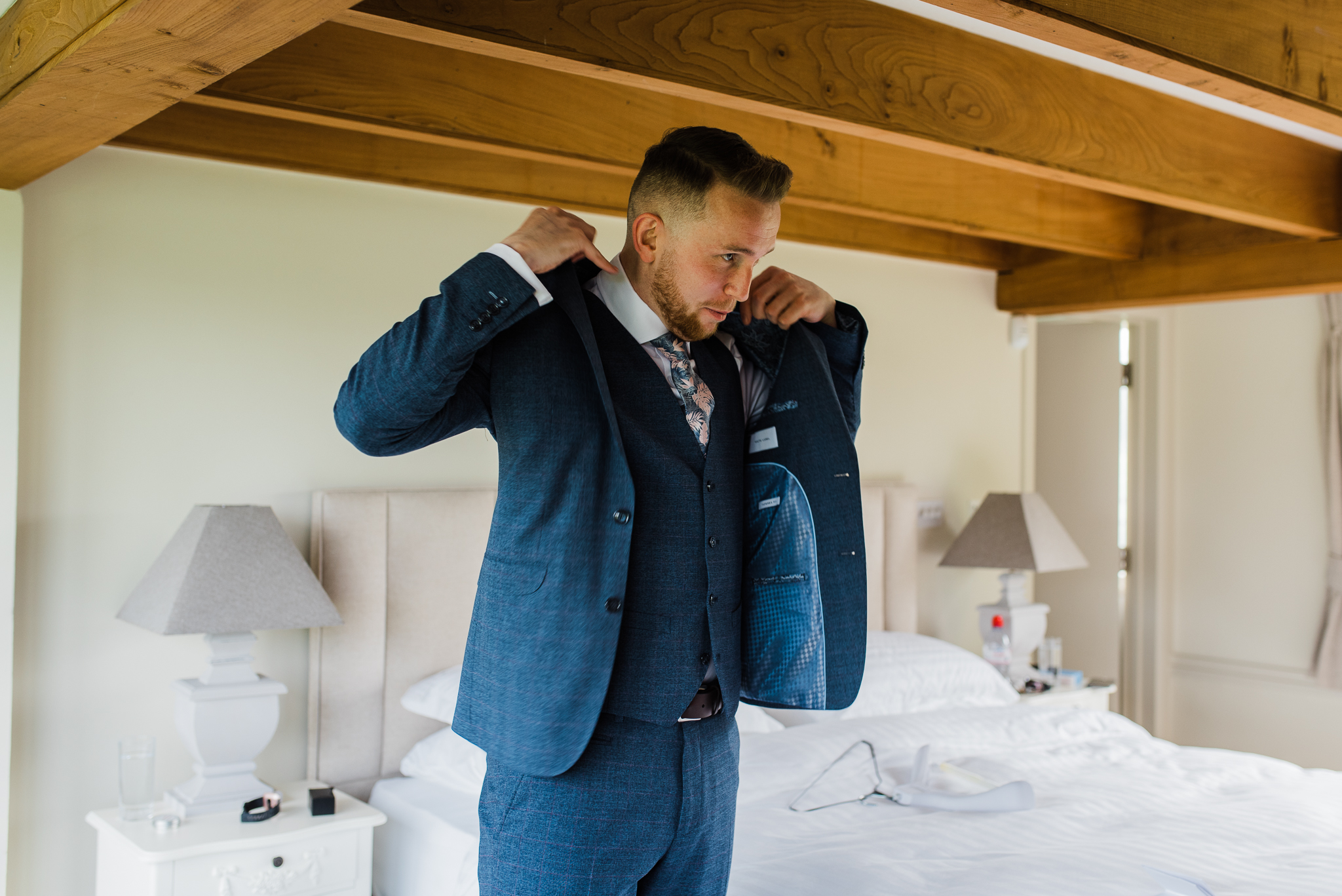 Groom putting on jacket in Lapstone Barn