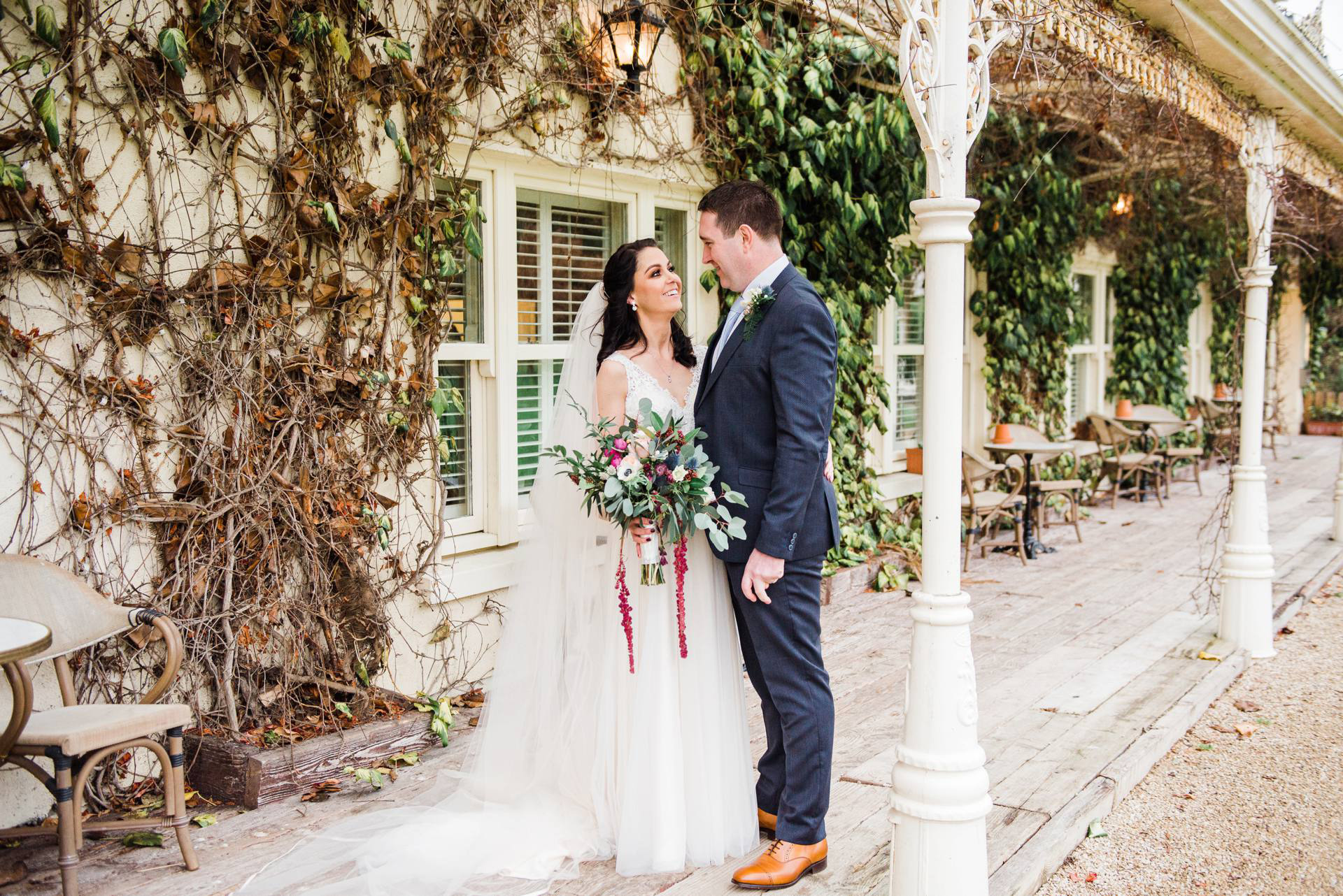 bride looks ta groom in front of ivy covered wall at brook lodge and Macreddan Village in Wicklow