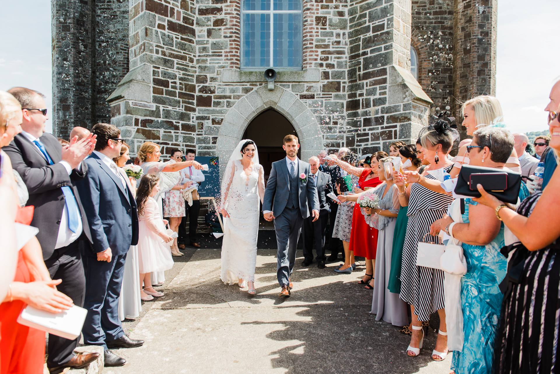 Bride and groom leave church with confetti around them