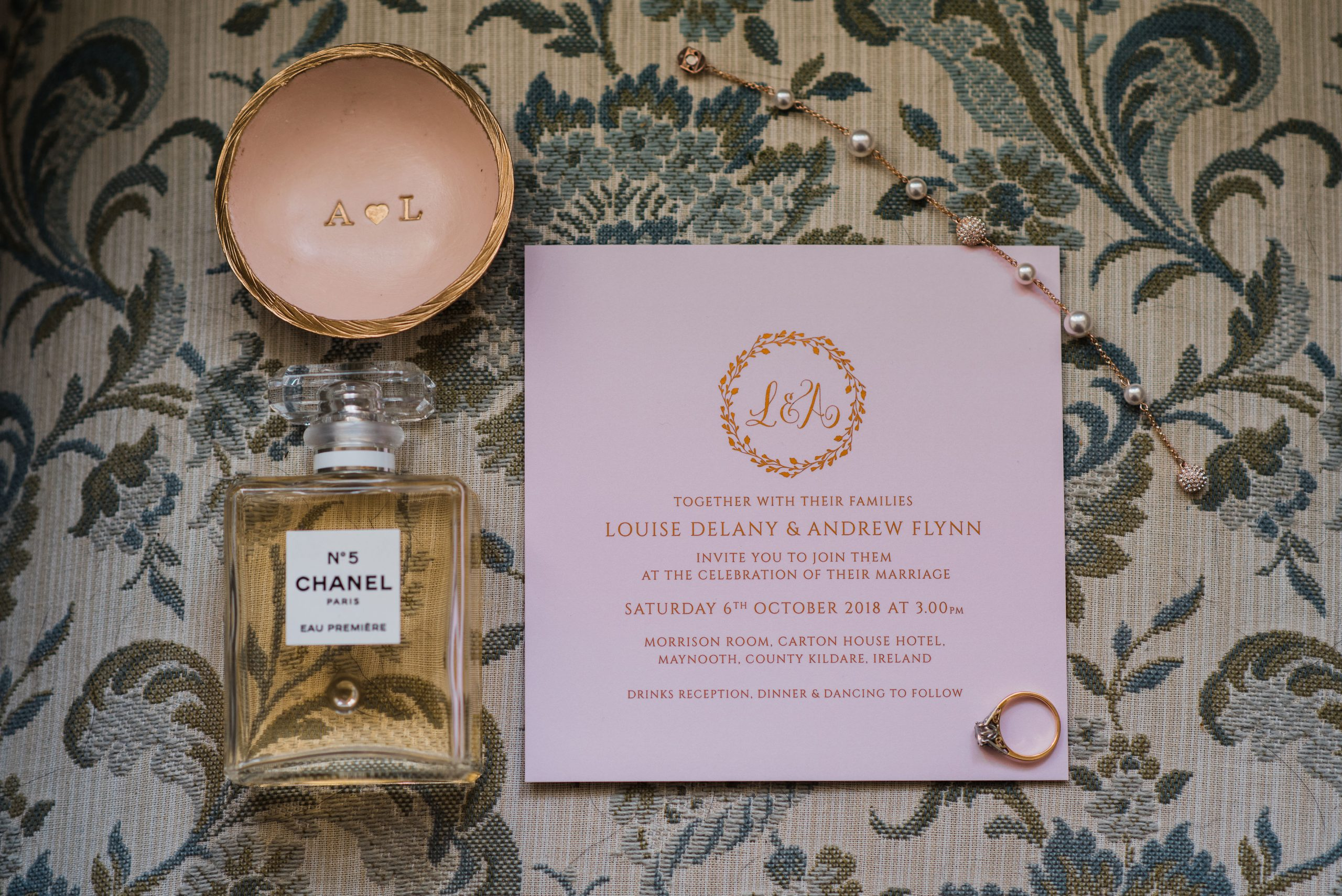 Pink wedding invitation lying beside Chanel perfume and ring dish