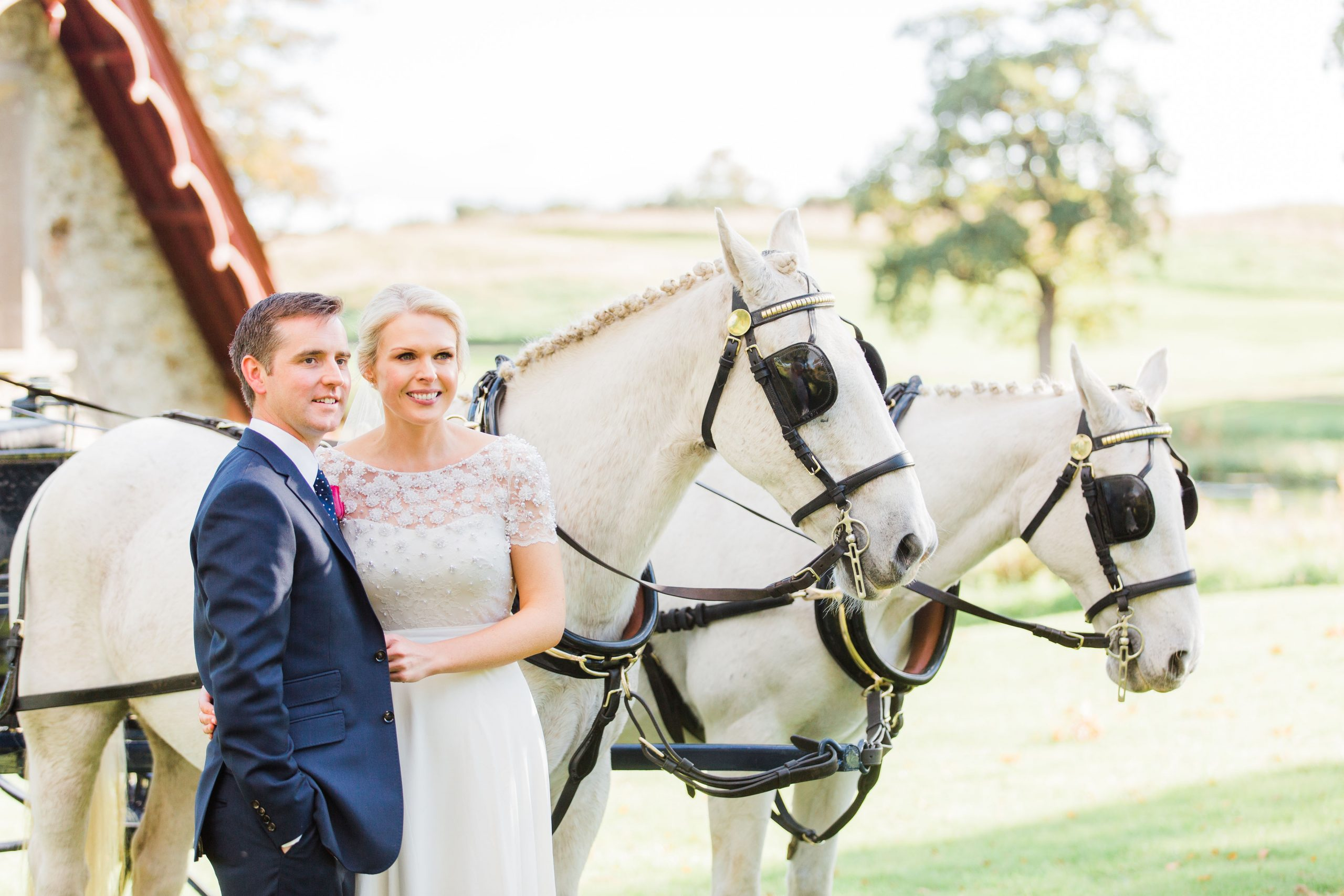 Bride and groom standing beside two white horses