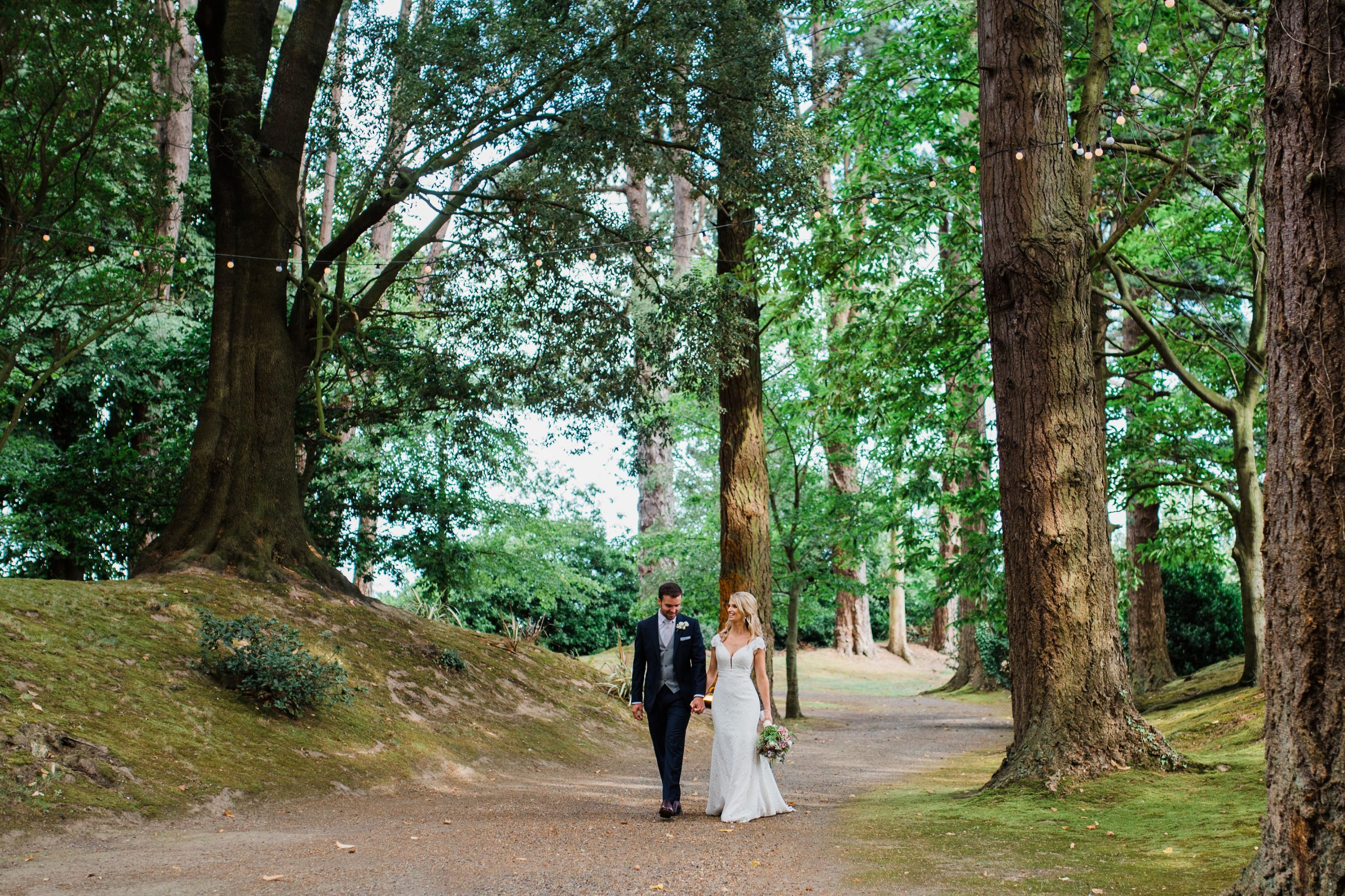 Bride and groom walking together through woods