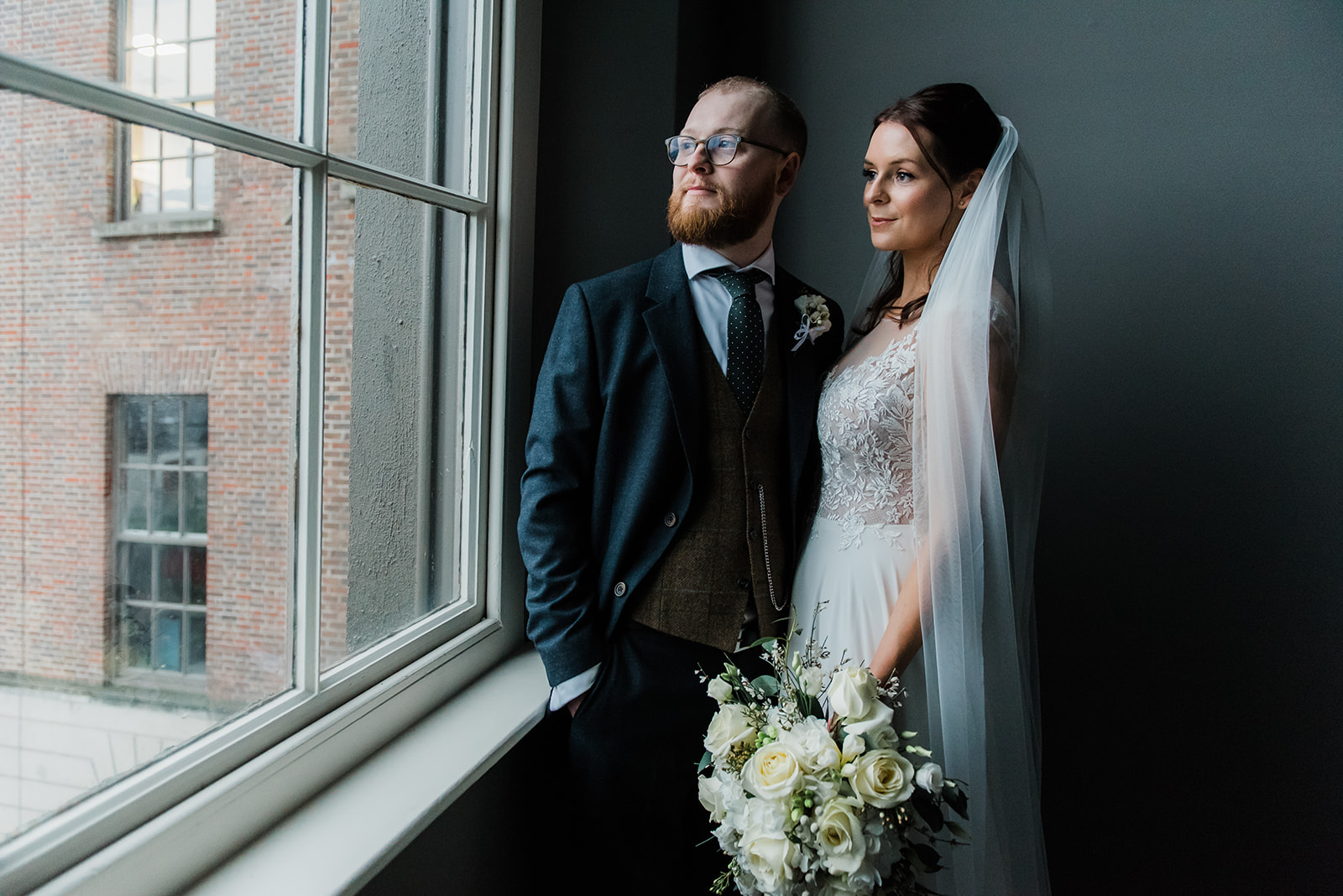 Bride and groom standing at window